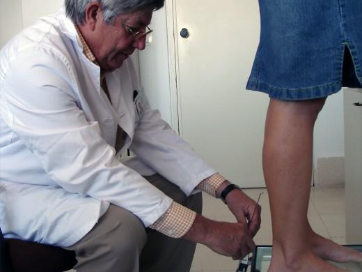 Felipe Martín revisa los pies de una paciente en la Consulta del Hospital